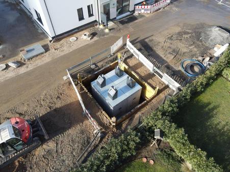 fertig eingesetzte Müllbehälter in den Betonboxen, in Baugrube mit Verbau
